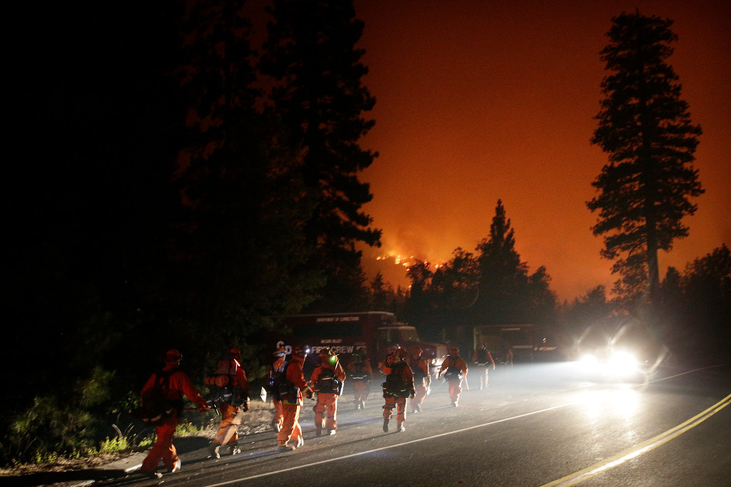Description of . Firefighters walk toward their trucks as the Rim Fire continues to burn near Yosemite National Park, Calif., on Saturday, Aug. 24, 2013. Fire crews are clearing brush and setting sprinklers to protect two groves of giant sequoias as a massive week-old wildfire rages along the remote northwest edge of Yosemite National Park. (AP Photo/Jae C. Hong)