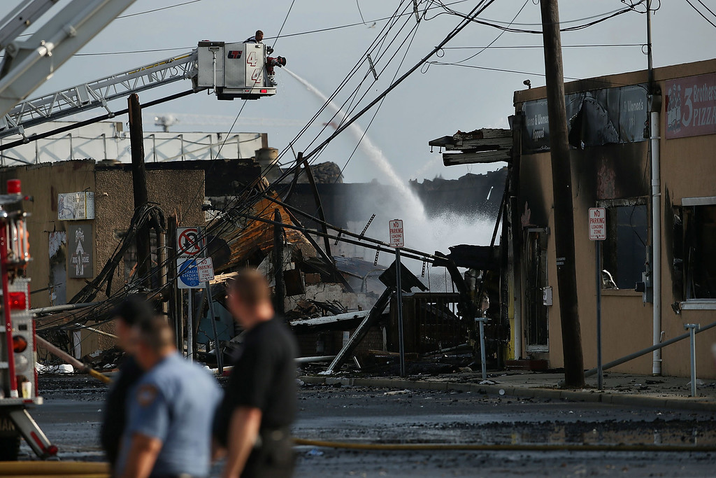 Description of . A firefighter sprays water on a hot-spot at the scene of a massive fire that destroyed dozens of businesses along an iconic Jersey shore boardwalk on September 13, 2013 in Seaside Heights, New Jersey.  (Photo by Spencer Platt/Getty Images)