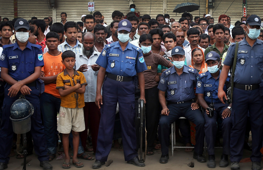 Description of . Policemen stand guard while a crowd gathers to watch workers toiling in a collapsed garment factory building on Tuesday, April 30, 2013 in Savar, near Dhaka, Bangladesh.  (AP Photo/Wong Maye-E)