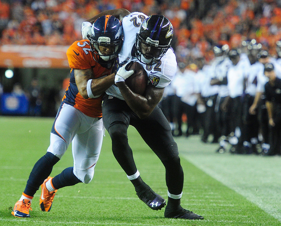 Description of . Denver Broncos defensive back Tony Carter (32) tries to tackle Baltimore Ravens wide receiver Torrey Smith (82) before he makes it to the end zone. (Photo by AAron Ontiveroz/The Denver Post)