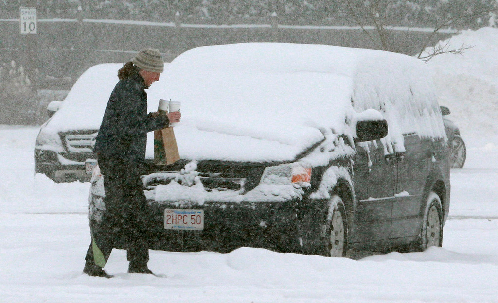 Description of . A shopper walks through a snow-covered parking lot Wednesday morning, Feb. 5, 2014, in Sudbury, Mass. Up to a foot of snow was predicted through the day in many parts of Massachusetts.(AP Photo/Bill Sikes)
