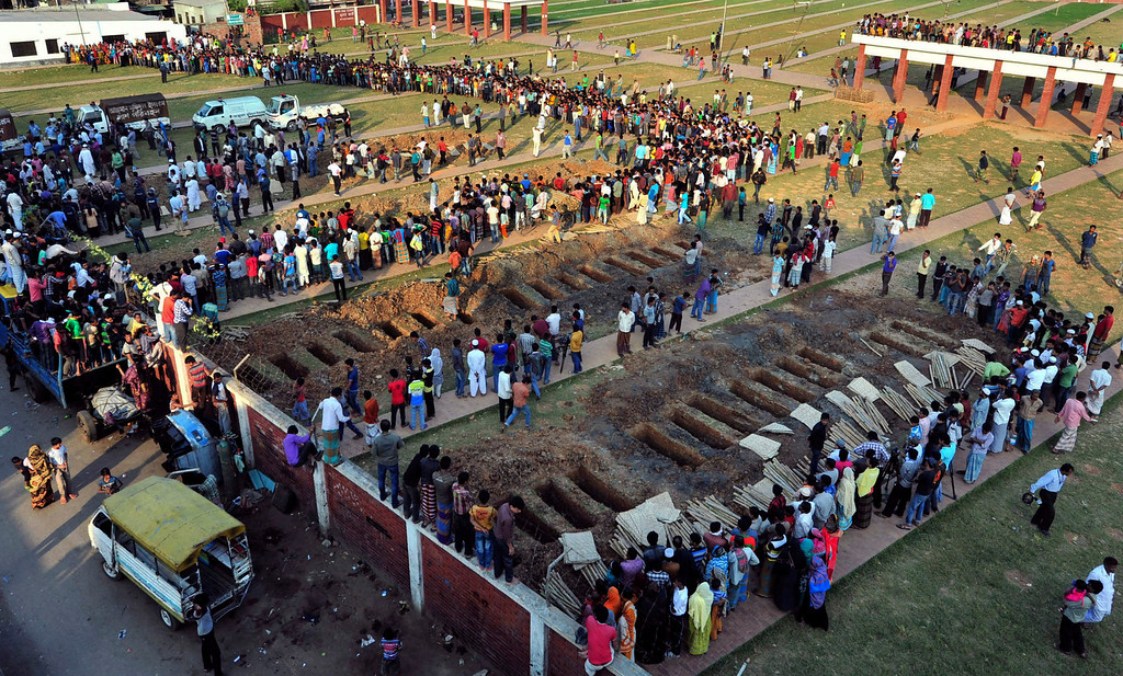 . In this Nov. 27, 2012 file photo, people prepare to bury the bodies of some of the 112 victims of a garment factory fire in Dhaka, Bangladesh.  (AP Photo/Khurshed Rinku, File)