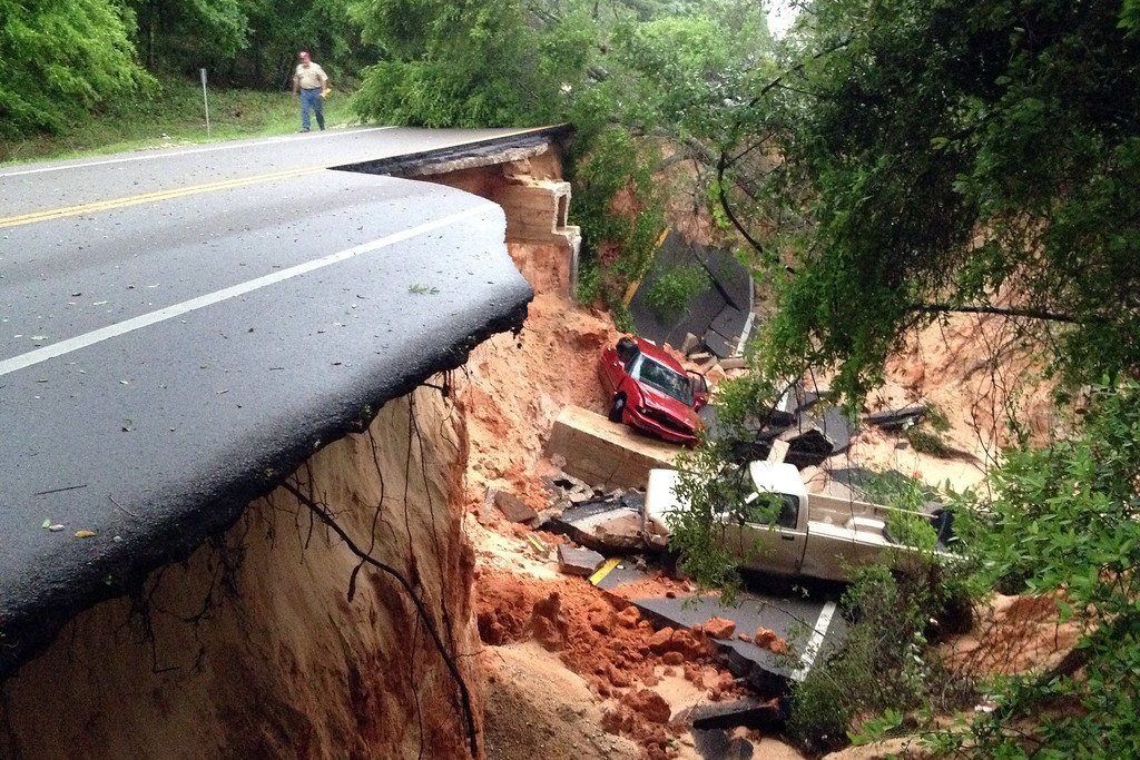 Description of . In this Wednesday April 30, 2014 file photo, a man walks near a portion of the Scenic Highway collapsed near Pensacola, Fla. (AP Photo/Pensacola News Journal, Katie E. King, File)