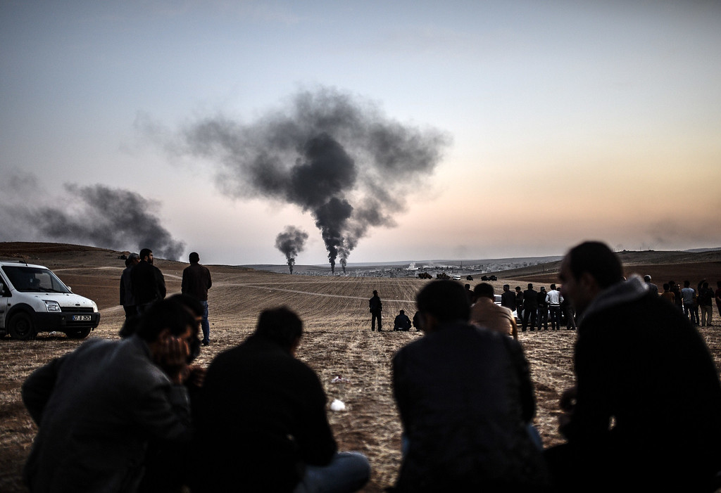 Description of . People watch as smokes rises from the town of Kobane, also known as Ain al-Arab, on October 26, 2014, at the Turkish border near the southeastern village of Mursitpinar, Sanliurfa province. Turkish President Recep Tayyip Erdogan accused the main Kurdish party in Syria of not wanting Kurdish peshmerga fighters from Iraq to help it fight Islamic State jihadists trying to overrun the town of Kobane, reports said October 26, 2014. Erdogan said that the Syrian Kurdish party the Democratic Union Party (PYD), which has been leading the defence of Kobane, fears losing its influence in northern Syria when the peshmerga arrive in the coming days. BULENT KILIC/AFP/Getty Images