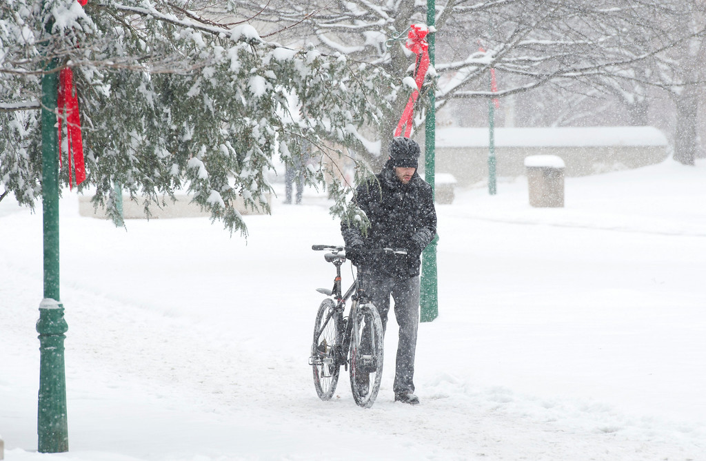 Description of . A bicyclist walks his bike through the snow on the Indiana University campus in Bloomington, Ind. Friday, Dec. 6, 2013. The National Weather Service has issued a winter storm warning and is predicting about 10 inches of snow by midnight Friday.  (AP Photo, Bloomington Herald-Times, David Snodgress)