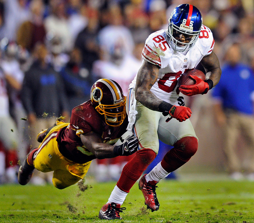 Description of . Washington Redskins inside linebacker London Fletcher reaches to stop New York Giants tight end Martellus Bennett (85) during the first half of an NFL football game in Landover, Md., Monday, Dec. 3, 2012. (AP Photo/Nick Wass)