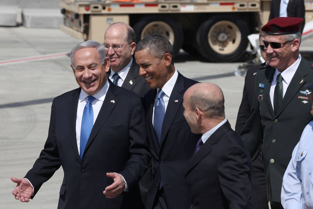 Description of . U.S. President Barack Obama (C) is greeted by Israeli Prime Minister Benjamin Netanyahu (L) and Defense Minister Moshe Ya'alon (2L) during an official welcoming ceremony on his arrival at Ben Gurion International Airport on March, 20, 2013 near Tel Aviv, Israel. (Photo by Marc Israel Sellem-Pool/Getty Images)