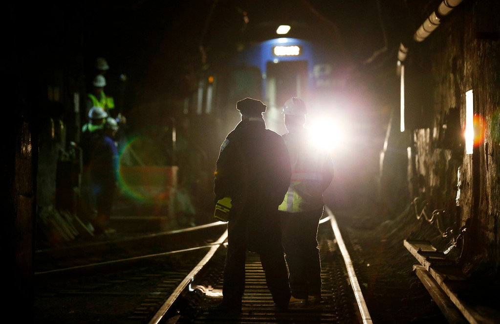 Description of . John Burkhard, right, assistant superintendent for the Way and Structures Division of the Port Authority Trans-Hudson train line, stands next to a police officer as a PATH train passes in the tunnel, Tuesday, Nov. 27, 2012, in Hoboken, N.J. While parts of the trans-Hudson service have gradually returned to operation since Superstorm Sandy, the Hoboken station has been closed, leaving thousands of commuters to seek alternatives. (AP Photo/Julio Cortez)