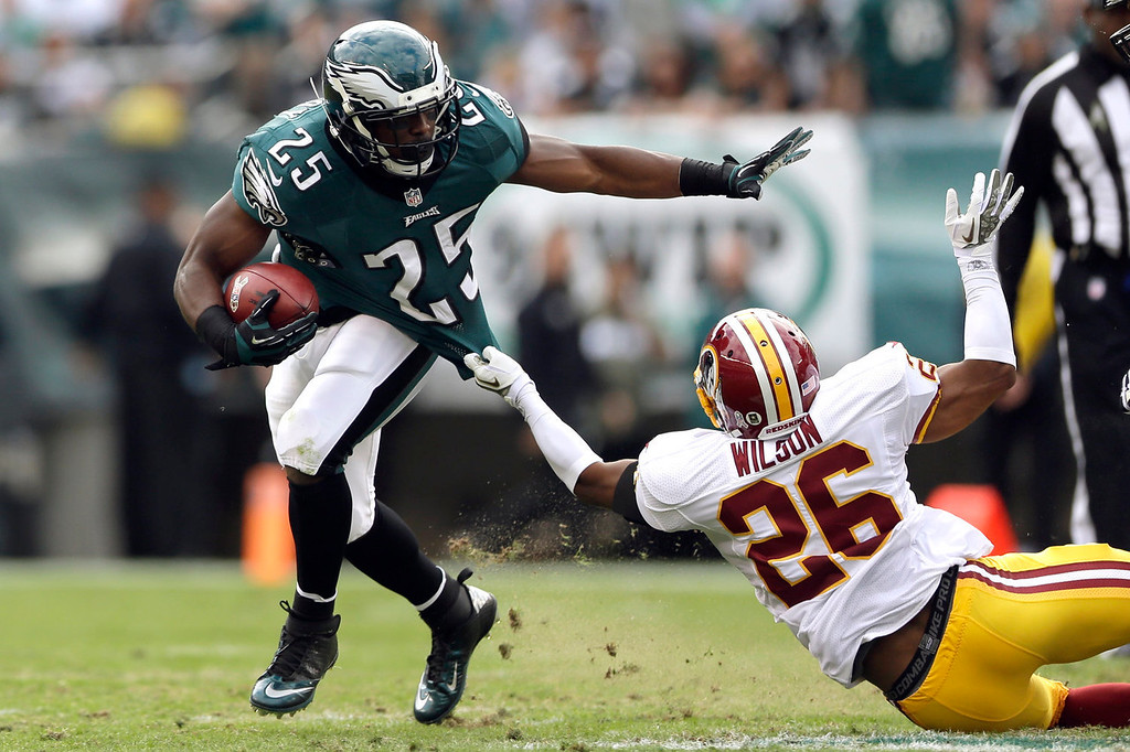 Description of . Philadelphia Eagles' LeSean McCoy (25)is dragged to the turf by Washington Redskins cornerback Josh Wilson during the first half of an NFL football game in Philadelphia, Sunday, Nov. 17, 2013. (AP Photo/Matt Rourke)