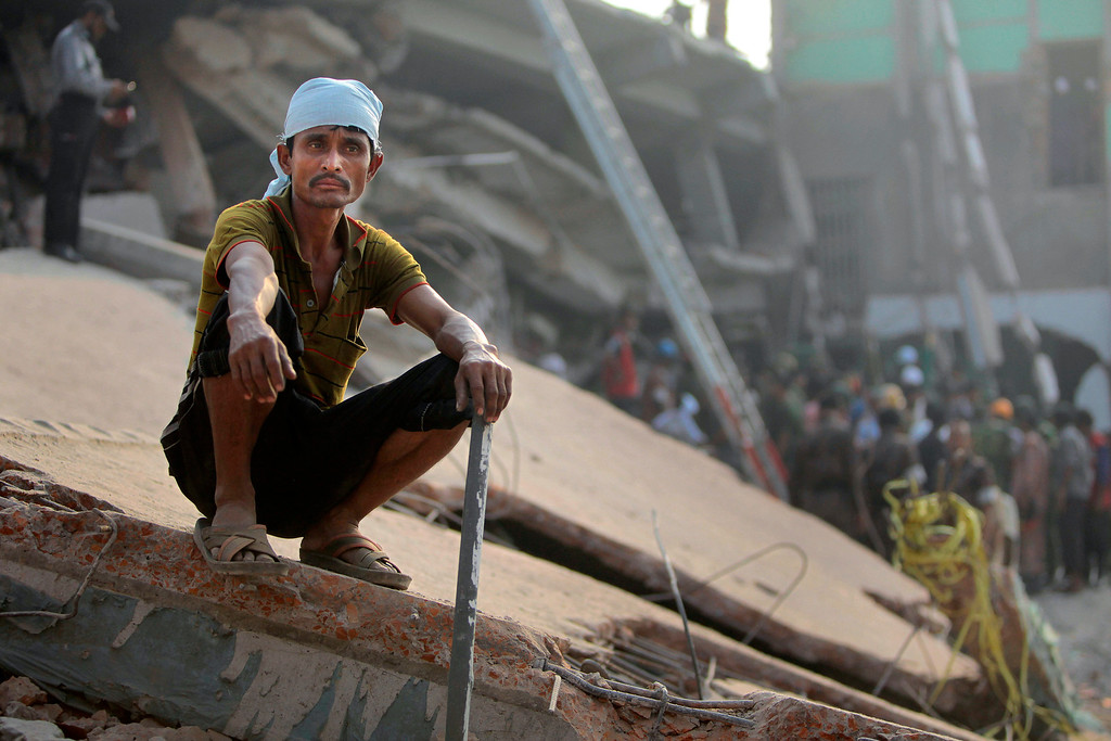 Description of . A Bangladeshi rescue worker takes a break at the site of a building that collapsed Wednesday in Savar, near Dhaka, Bangladesh,Thursday, April 25, 2013.   (AP Photo/A.M.Ahad)