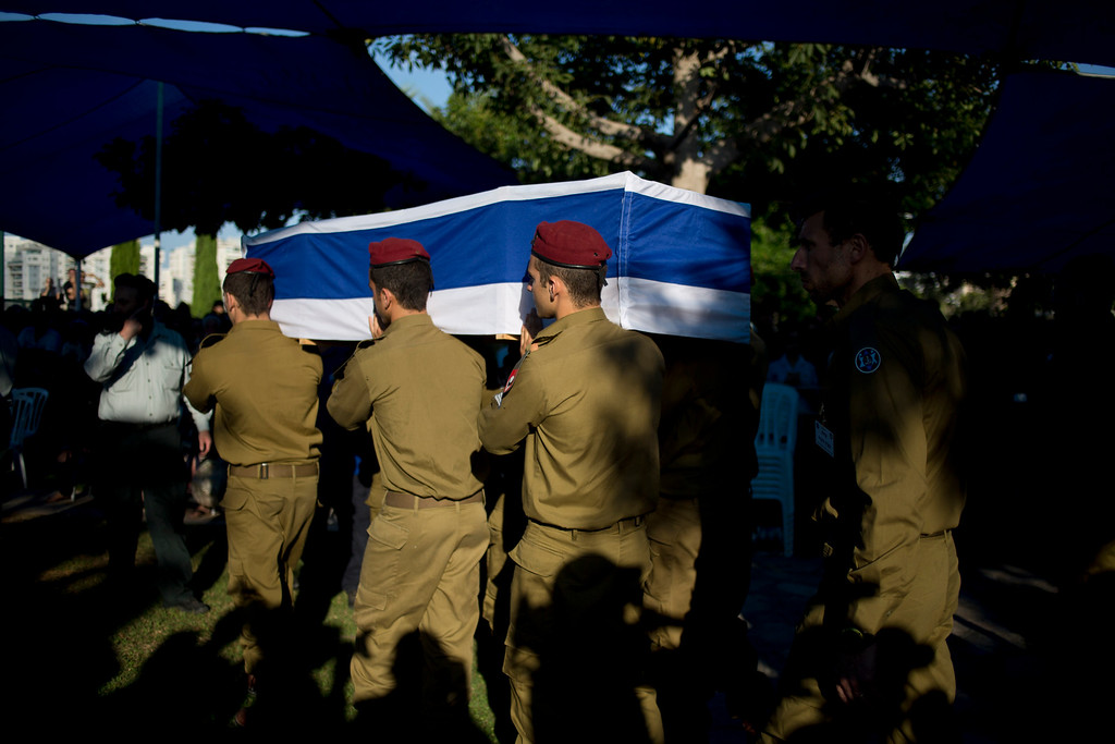 Description of . Israeli soldiers of the Maglan elite unit carry the coffin of Staff Sgt. Matan Gotlib, a Maglan elite unit soldier, during his funeral in the military cemetery in Rishon Letzion, central Israel, Thursday, July 31, 2014. Gotlib, 21, was killed in combat on Wednesday in the southern Gaza Strip. (AP Photo/Ariel Schalit)