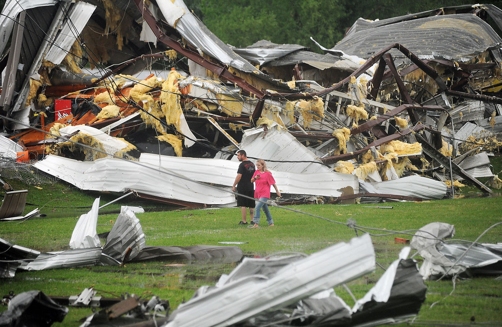 Description of . A man and woman examine the twisted wreckage of Glass Masters on U.S. 49 Frontage Road in Richland,  Miss., shortly after it was destroyed by a tornado late Monday afternoon, April 28, 2014.   With parts of the U.S. recovering from deadly tornadoes, more heavy storms are making their way across the South.  (AP Photo/The Clarion-Ledger, )