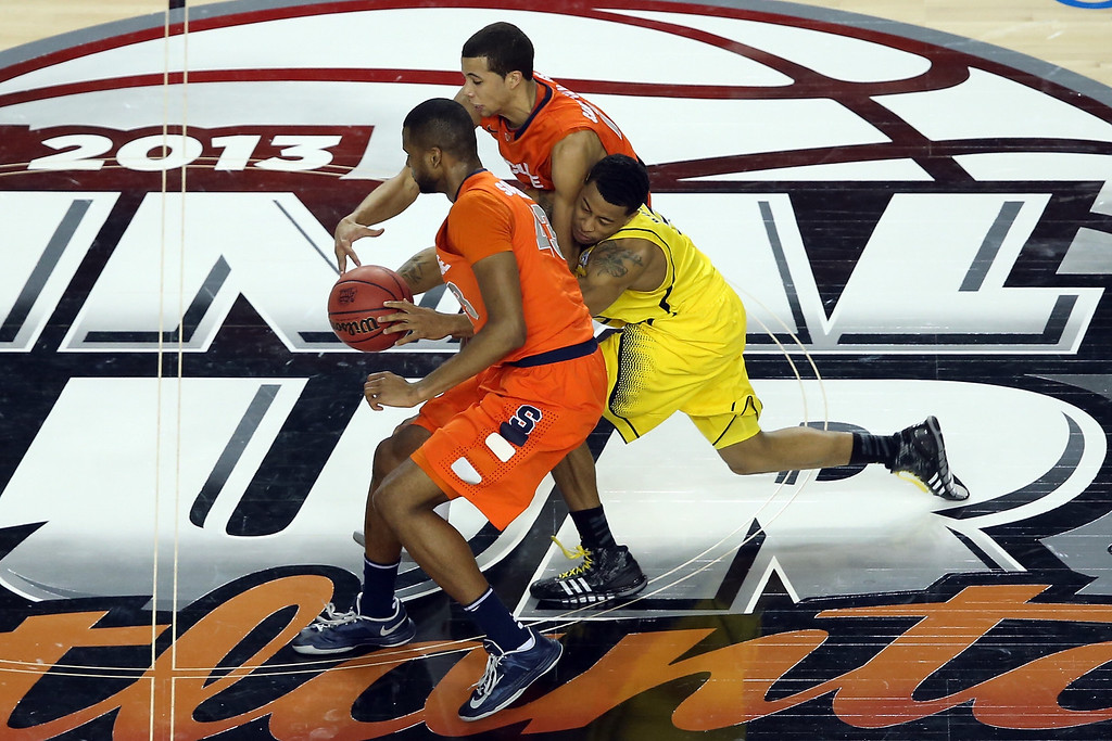 Description of . ATLANTA, GA - APRIL 06:  Trey Burke #3 of the Michigan Wolverines chases down a looseball in the first half against Michael Carter-Williams #1 and James Southerland #43 of the Syracuse Orange during the 2013 NCAA Men's Final Four Semifinal at the Georgia Dome on April 6, 2013 in Atlanta, Georgia.  (Photo by Andy Lyons/Getty Images)