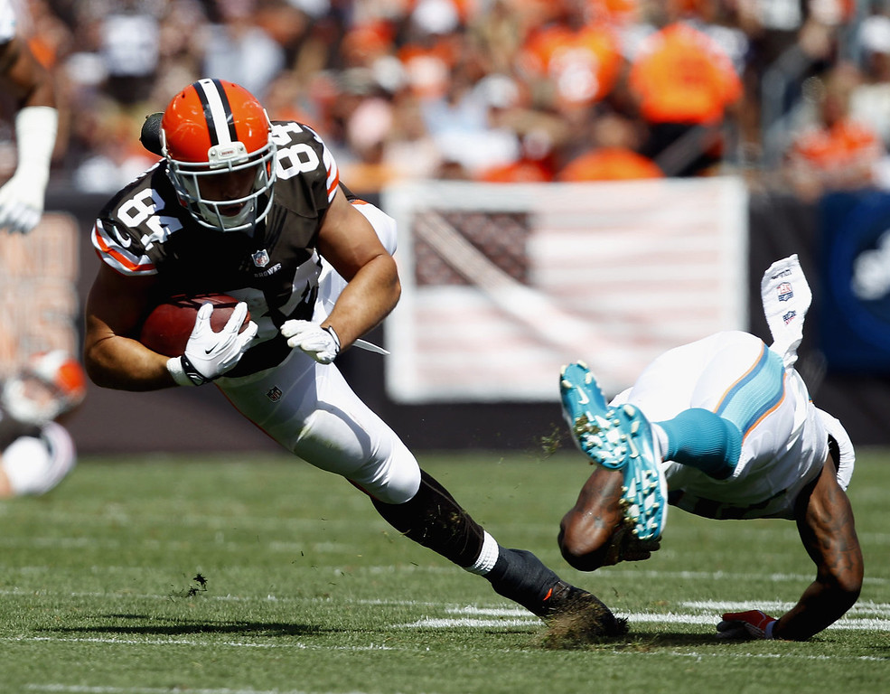 Description of . Tight end Jordan Cameron #84 of the Cleveland Browns dives for extra yardage after being hit by safety Reshad Jones #20 of the Miami Dolphins at Cleveland Browns Stadium on September 8, 2013 in Cleveland, Ohio. (Photo by Matt Sullivan/Getty Images)