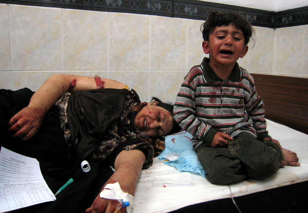 Description of . A child cries next to a person injured in an attack that lays in a hospital in Kirkuk, 290 kilometers (180 miles) north of Baghdad, Iraq, Saturday, March 10, 2007. A rocket hit an open market in central Kirkuk, killing two persons and injuring another 35, police said. (AP Photo/Emad Matti)