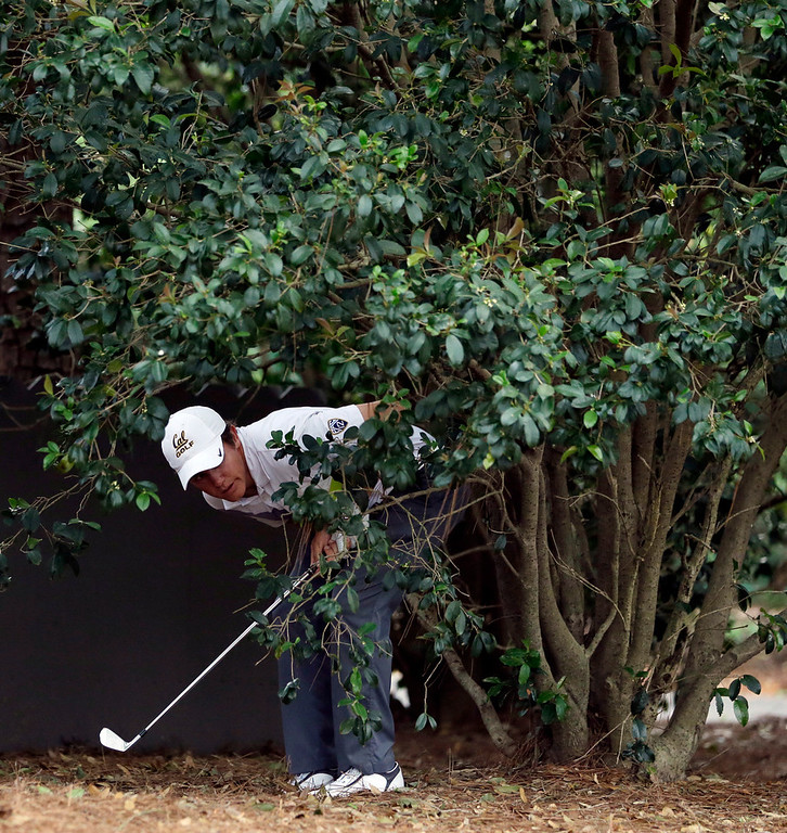 Description of . Amateur Michael Weaver looks around a tree before taking his shot in the rough off of the first fairway during the second round of the Masters golf tournament Friday, April 12, 2013, in Augusta, Ga. (AP Photo/Darron Cummings)