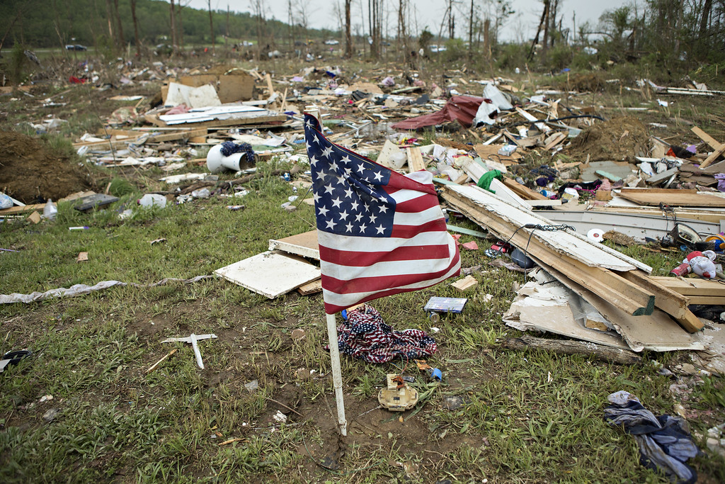 Description of . Flag that was found in debris was placed by volunteers working to help clean up after a strong tornado went through the area on April 27 for the second time in three years on April 28, 2014 in Vilonia, Arkansas. After deadly tornadoes ripped through the area and have left over a dozen dead, Mississippi, Arkansas, Texas, Louisiana, and Tennessee are all under watch as multiple storms over the next few days are expected.  (Photo by Wesley Hitt/Getty Images)