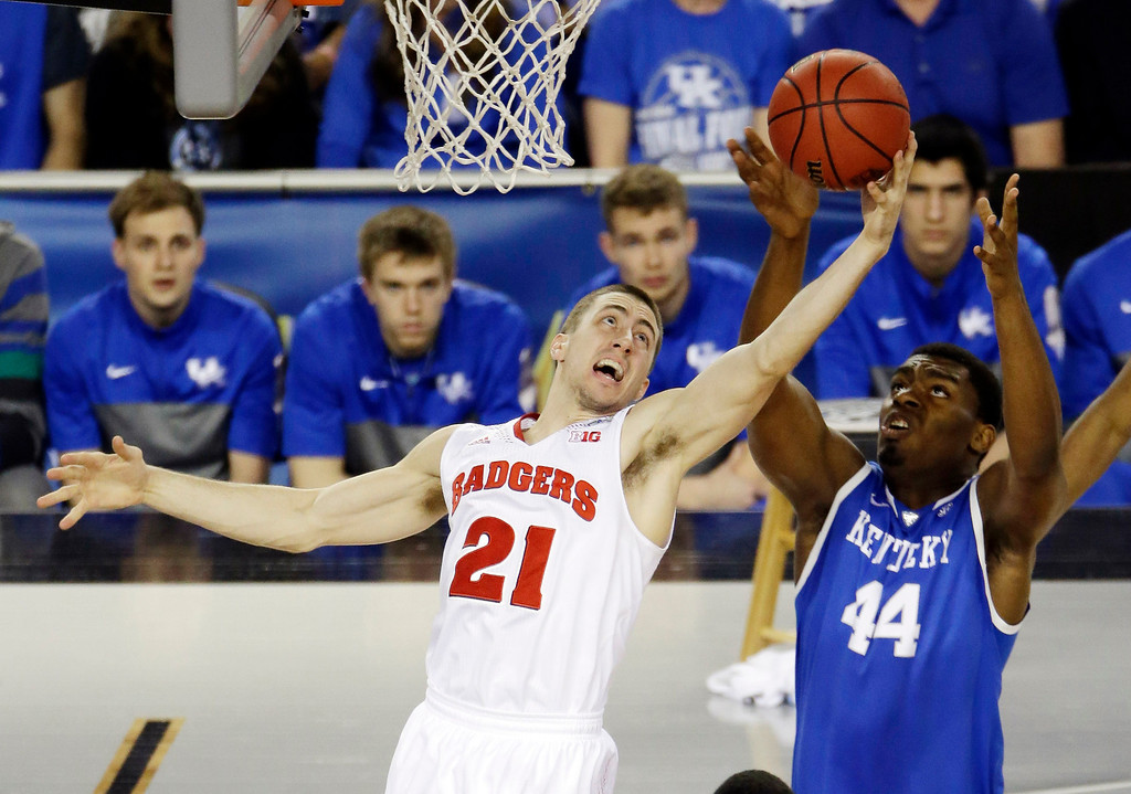 Description of . Wisconsin guard Josh Gasser (21) and Kentucky center Dakari Johnson (44) go after a rebound during the first half of the NCAA Final Four tournament college basketball semifinal game Saturday, April 5, 2014, in Arlington, Texas. (AP Photo/Tony Gutierrez)