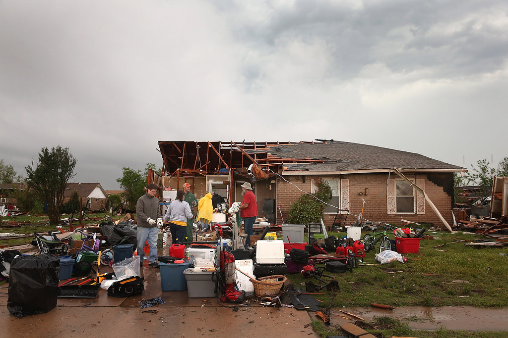 Description of . MOORE, OK - MAY 23:  Volunteers help a co-worker to salvage belongings from her home after it was destroyed by a tornado May 23, 2013 in Moore, Oklahoma. The two-mile wide EF5 tornado touched down May 20 killing at least 24 people and leaving behind extensive damage to homes and businesses. U.S. President Barack Obama promised federal aid to supplement state and local recovery efforts.  (Photo by Scott Olson/Getty Images)
