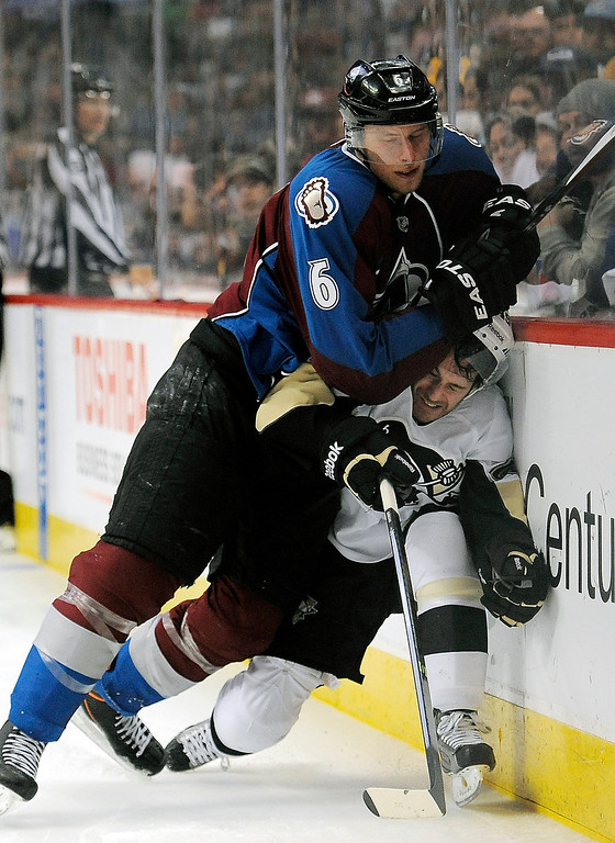 Description of . Colorado Avalanche defenseman Erik Johnson, top, checks Pittsburgh Penguins center Brian Gibbons against the boards during the second period of an NHL hockey game Sunday, April 6, 2014, in Denver.  (AP Photo/Chris Schneider)
