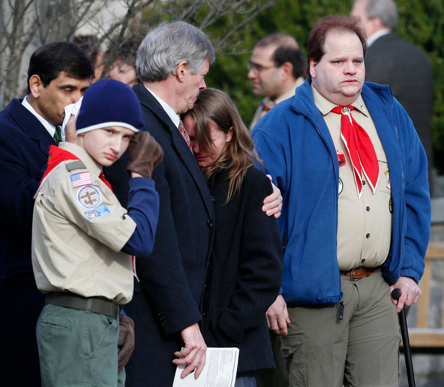 Description of . Mourners react outside of Trinity Episcopal Church after funeral services for Benjamin Andrew Wheeler Thursday, Dec. 20, 2012, in Newtown, Conn. Wheeler, 6, died when the gunman, Adam Lanza, walked into Sandy Hook Elementary School in Newtown, Dec. 14, and opened fire, killing 26 people, including 20 children, before killing himself. (AP Photo/Julio Cortez)