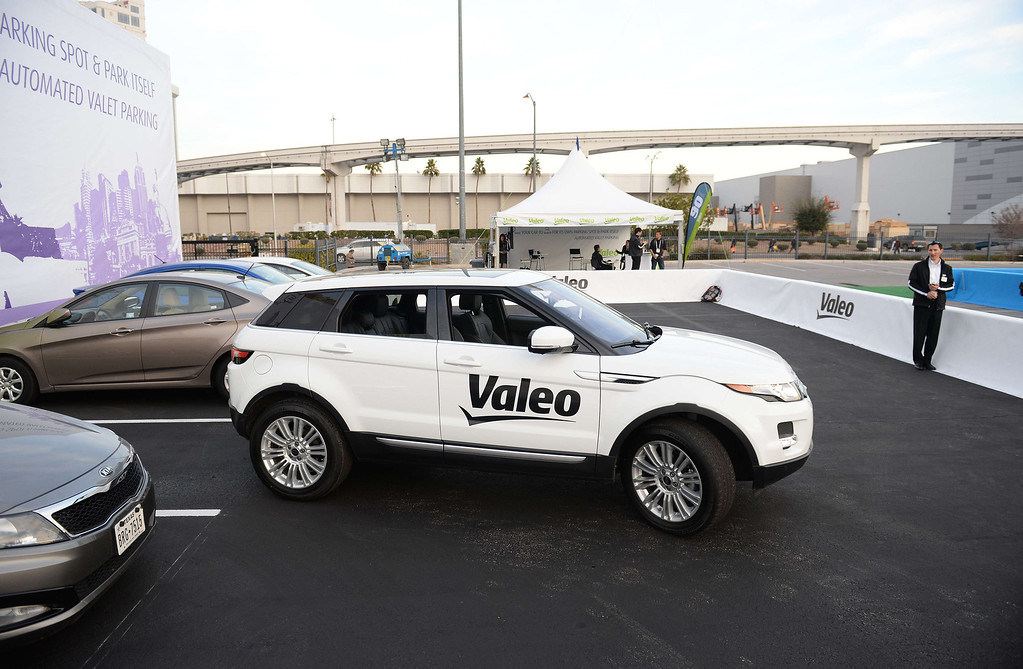 Description of . Valeo representative Nicolas Jecker (R) watches as a Range Rover Evoque equipped with Valeo self-parking technology backs into a parking spot during a driverless car demo at the 2014 International CES in Las Vegas, Nevada, January 8, 2014. The driverless parking is initiated with an iPhone app.  The car is equipped with 12 ultrasonic sensors, six in back and six in front, a laser scanner mounted in the grille, and four cameras.AFP PHOTO / Robyn Beck/AFP/Getty Images