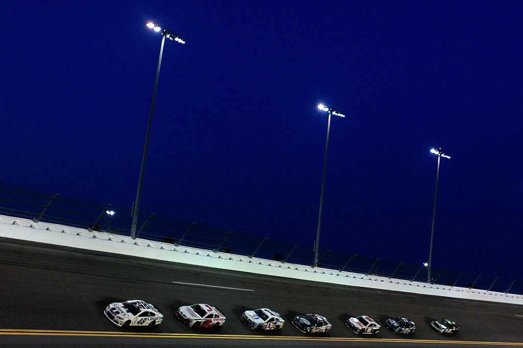 Description of . DAYTONA BEACH, FL - JULY 06:  Jimmie Johnson, driver of the #48 Lowe\'s Dover White Chevrolet, leads a pack of cars during the NASCAR Sprint Cup Series Coke Zero 400 at Daytona International Speedway on July 6, 2013 in Daytona Beach, Florida.  (Photo by Sean Gardner/Getty Images)