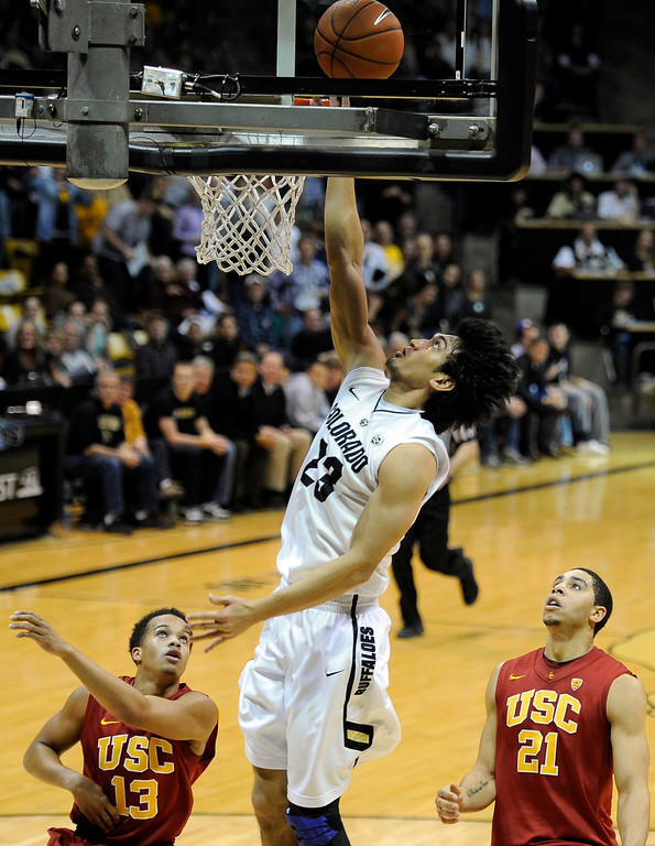 Description of . University of Colorado's Sabatino Chen goes for a layup over Chass Bryan, No. 13, and Aaron Fuller, No. 21, during a game against the University of Southern California on Thursday, Jan. 10, at the Coors Event Center on the CU campus in Boulder. Jeremy Papasso/Daily Camera