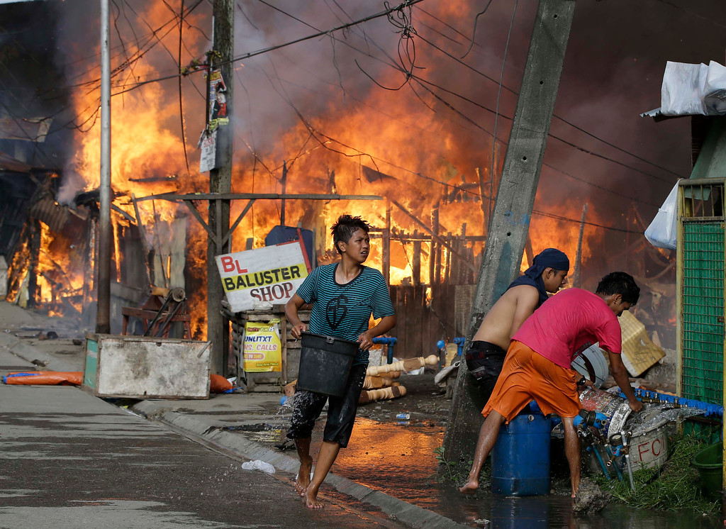 Description of . Residents try to put out a fire that gutted several homes while government troopers continue their assault on Muslim rebels Thursday, Sept. 12, 2013, in Zamboanga city in the southern Philippines. (AP Photo/Bullit Marquez)