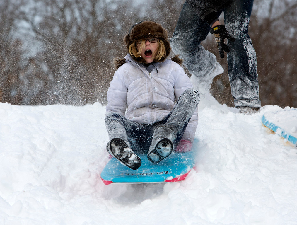 Description of . Mekenzie Bartone, 10, of Norfolk, Va., takes off down the hill on a sled at Northside Community Park in Norfolk on Wednesday, Jan. 29, 2014. The coast of Virginia was blanketed in up to 10 inches of snow Wednesday, with many workers in the heavily populated Hampton Roads region being told to stay home rather than travel to work in dangerous conditions. (AP Photo/The Virginian-Pilot, The' N. Pham)