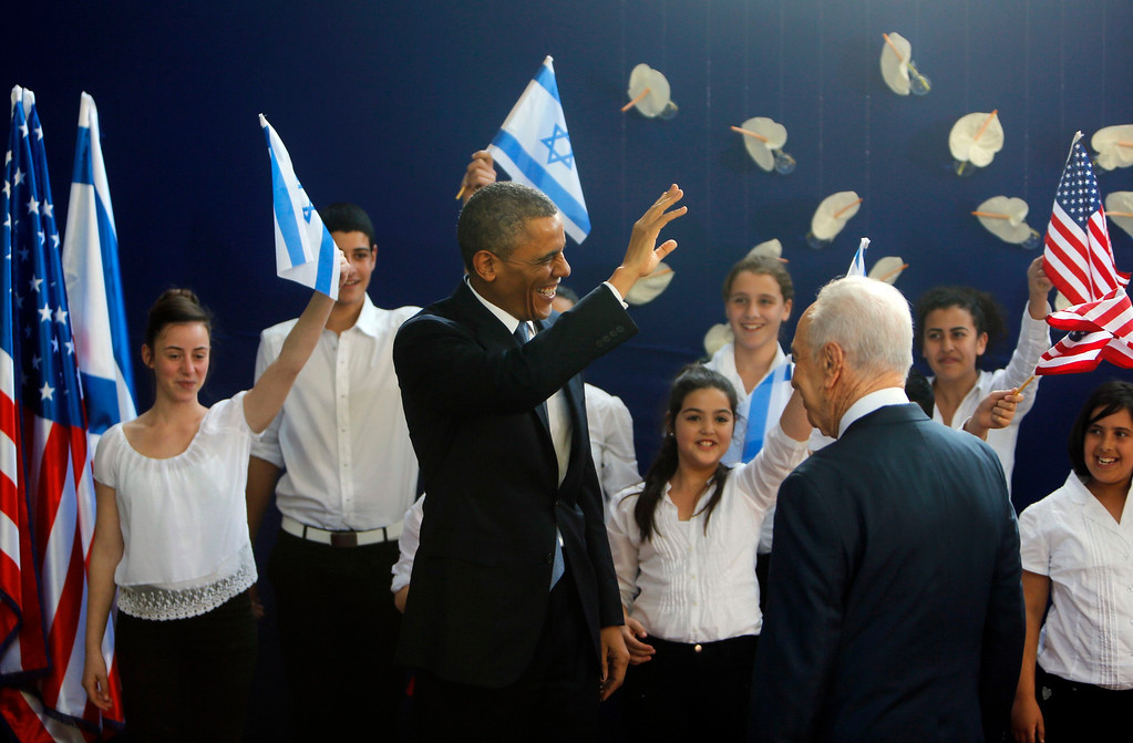 Description of . U.S. President Barack Obama waves as he stands with Israel's President Shimon Peres (back to camera) during a welcoming ceremony at Peres' residence in Jerusalem March 20, 2013.  REUTERS/Ronen Zvulun