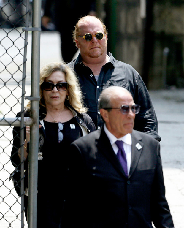 Description of . Chef Mario Batali, background center, walks out of Cathedral Church of Saint John the Divine after funeral services actor James Gandolfini, Thursday, June 27, 2013, in New York. (AP Photo/Julio Cortez)