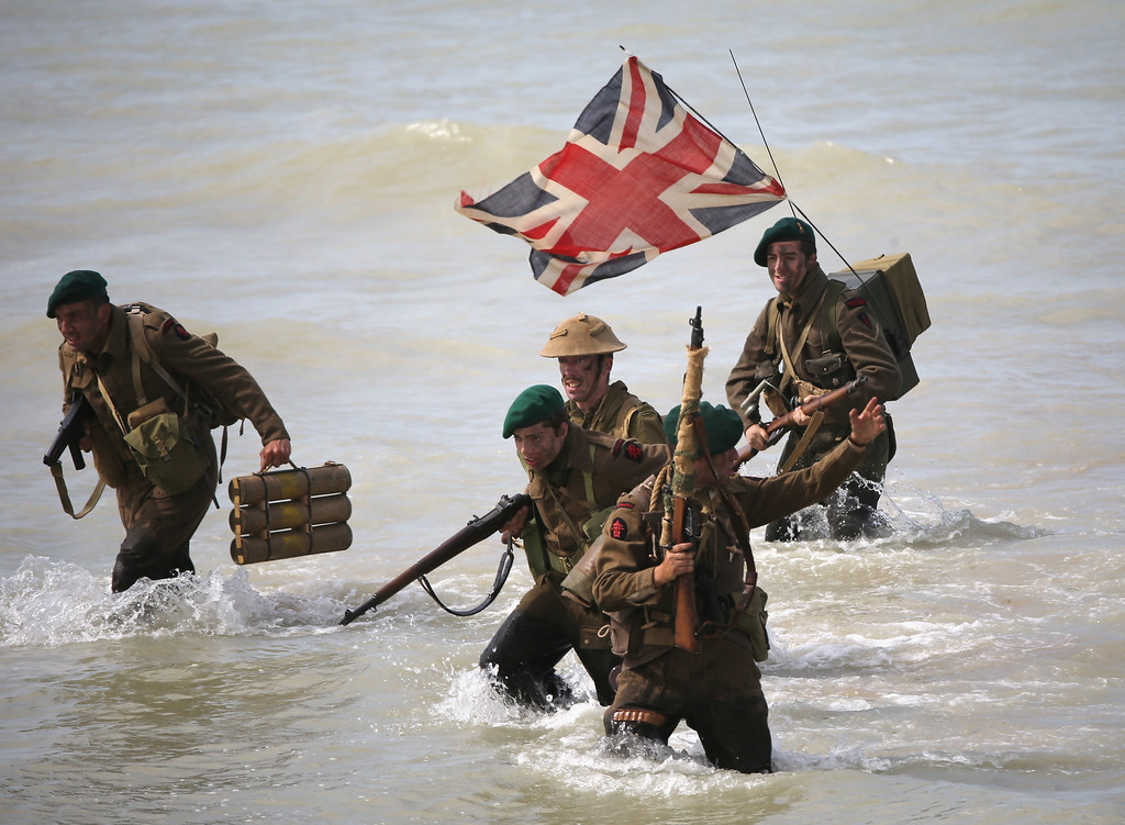 Description of . Re-enactors storm Gold Beach from a Royal Marine Landing craft during the 70th anniversary of the D-Day landings parade on June 6, 2014 in Arromanches Les Bains, France.   (Photo by Christopher Furlong/Getty Images)