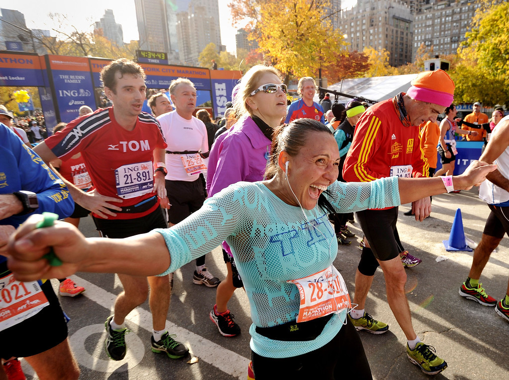 Description of . A woman and other runners cross the finish line at the New York City Marathon on November 3, 2013 in New York.   STAN HONDA/AFP/Getty Images