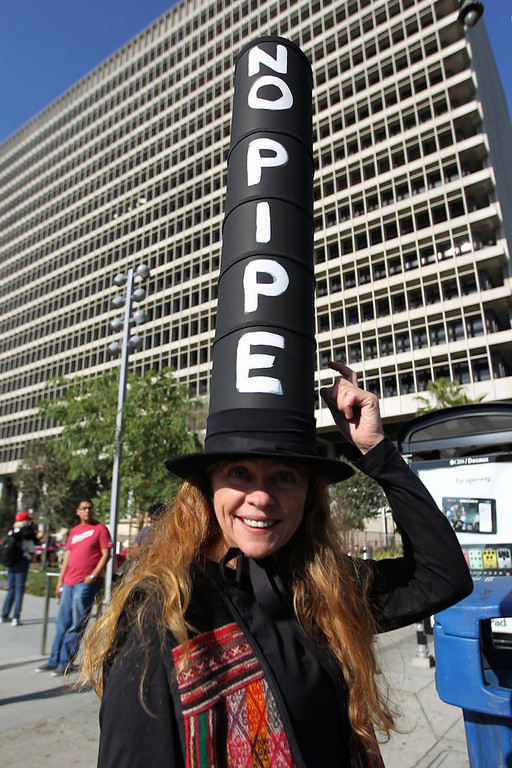 Description of . Elizabeth Lerer wears a pipe-shaped hat to express her opposition to the controversial Keystone XL Pipeline during the