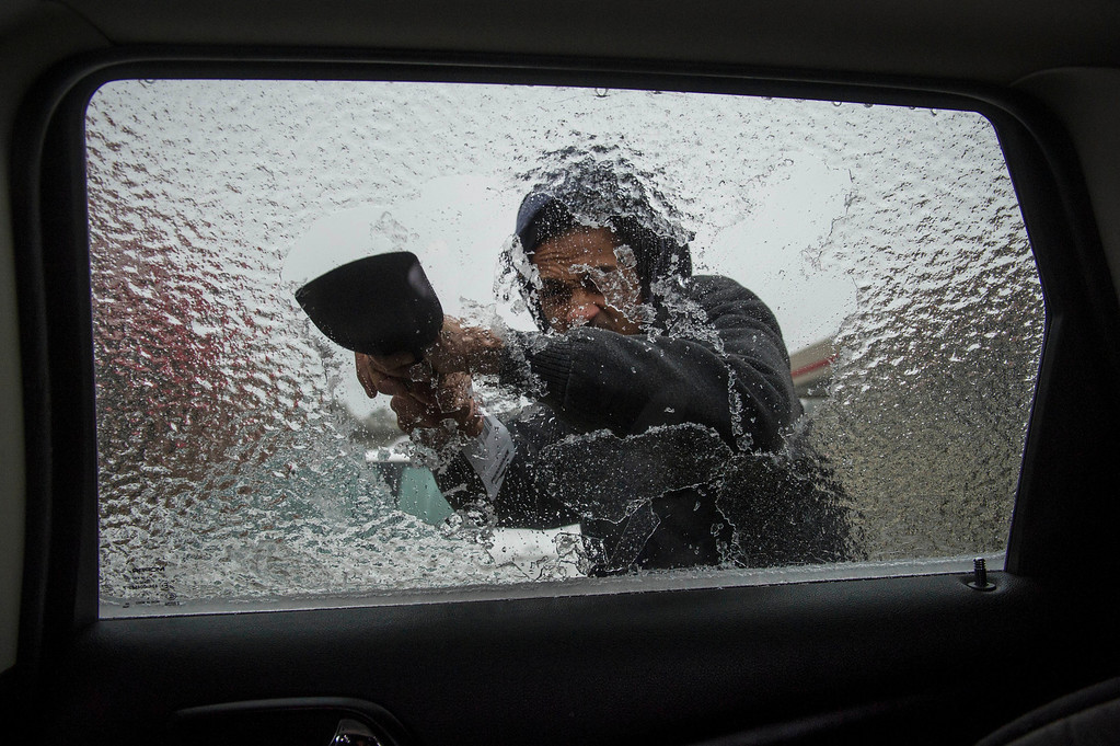 Description of . Lamarr Lewis scrapes ice from his car window during a winter storm on Wednesday, Feb. 12, 2014, in Doraville, Ga. (AP Photo/John Amis)