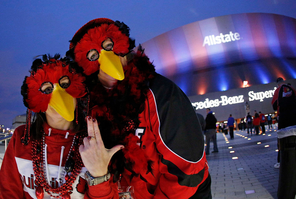 Description of . Louisville Cardinals fans wear mascot masks outside the Superdome before the Cardinals play the Florida Gators in their 2013 Allstate Sugar Bowl NCAA football game in New Orleans, Louisiana January 2, 2013.   REUTERS/Jonathan Bachman (UNITED STATES  - Tags: SPORT FOOTBALL)