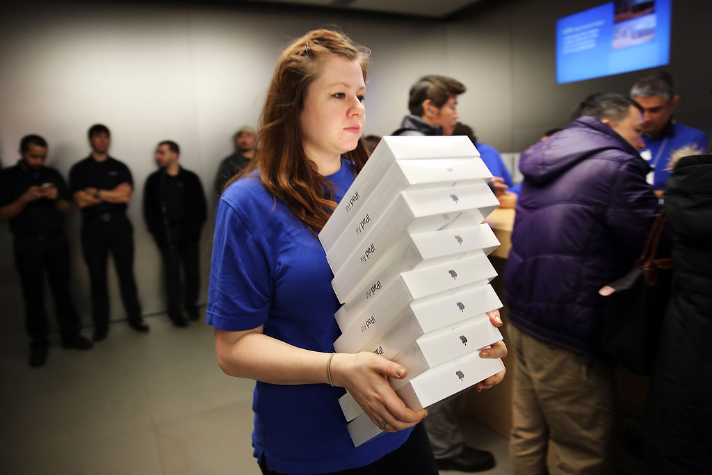 Description of . An Apple employee carries boxes of the new iPad Air at the Apple store on November 1, 2013 in New York City. (Photo by Spencer Platt/Getty Images)