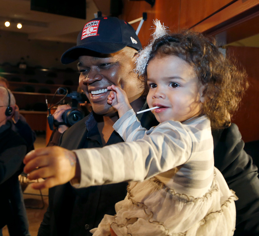 Description of . Chicago White Sox slugger Frank Thomas holds his two-year-old daughter Ashley after a news conference about his selection into the MLB Baseball Hall Of Fame Wednesday, Jan. 8, 2014, at U.S. Cellular Field in Chicago. Thomas joins Greg Maddux and Tom Glavine as first ballot inductees Wednesday, and will be inducted in Cooperstown on July 27 along with managers Bobby Cox, Joe Torre and Tony La Russa, elected last month by the expansion-era committee. (AP Photo/Charles Rex Arbogast)