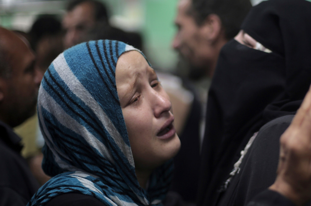 Description of . Palestinians grieve the death of their relatives who were killed in an Israeli strike at a U.N. school in Jebaliya refugee camp, at the Kamal Adwan hospital in Beit Lahiya, northern Gaza Strip, Wednesday, July 30, 2014. Israeli tank shells slammed into a crowded U.N. school Wednesday sheltering Gazans displaced by fighting, killing more than a dozen and wounding tens after tearing through the walls of two classrooms, a spokesman for a U.N. aid agency and a health official said. (AP Photo/Khalil Hamra)