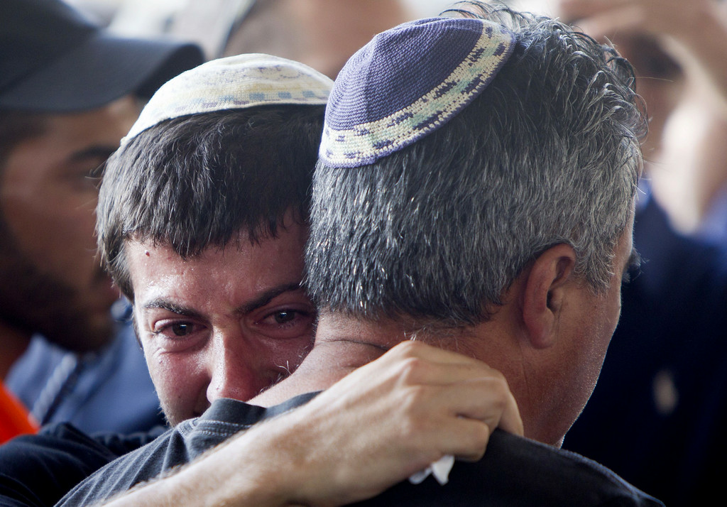 Description of . Relatives of Dror Khenin grieve on July 16, 2014, during his funeral in Yehud, east of Tel Aviv, the day after he was killed when a short-range rocket fired by Palestinian militants landed near the border with the Gaza Strip where he was delivering food to the Israeli soldiers. He is the first Israeli civilian killed during Israel's Operation Dove. Israel's campaign, now in its ninth day, has killed 214 Palestinians, with a Gaza-based rights group saying over 80 percent of them were civilians. AFP PHOTO/AHMAD  GHARABLI/AFP/Getty Images