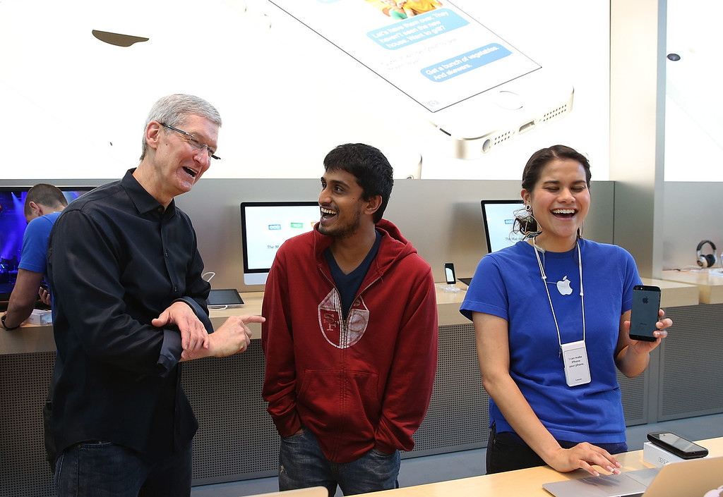 Description of . Apple CEO Tim Cook (L) meets with a customer purchasing the new iPhone on September 20, 2013 in Palo Alto, California.  (Photo by Justin Sullivan/Getty Images)