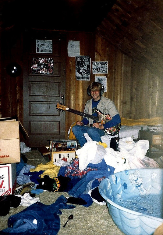 Description of . In this undated photo provided by Kim Cobain, a young Kurt Cobain plays guitar in his childhood home in Aberdeen, Wash.  Cobain's mother, Wendy O'Connor, is putting the 1.5-story Aberdeen bungalow _ which is assessed at less than $67,000 _ on the market for $500,000. But she'd also be happy entering into a partnership with anyone who wants to turn it into a museum. (AP Photo/Courtesy Kim Cobain)