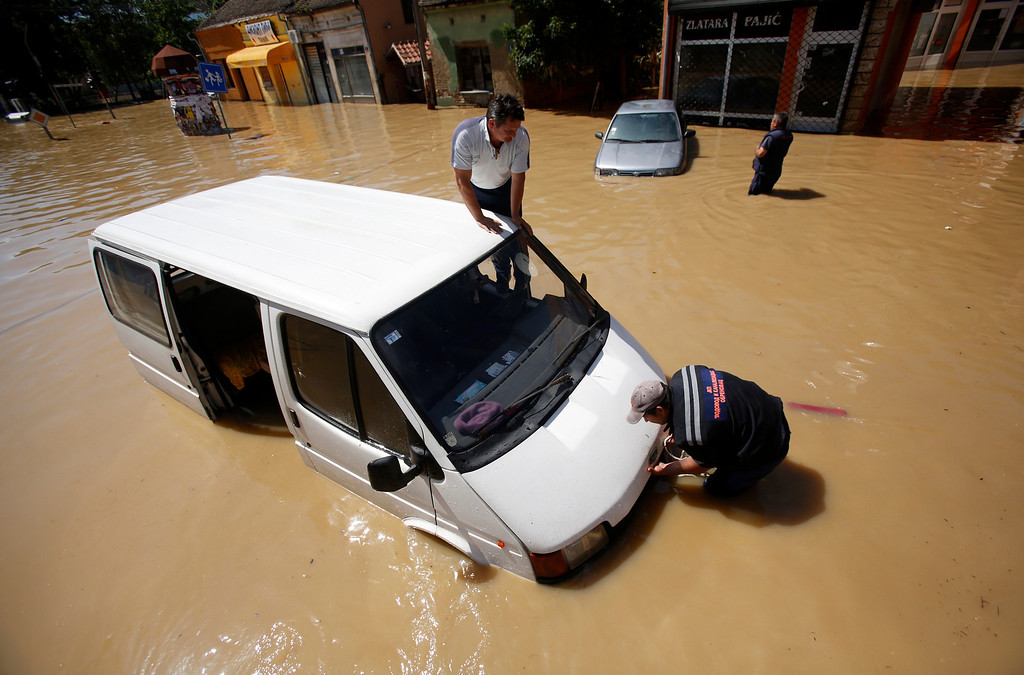 Description of . Two men trying to restart their van stuck in a flooded street in Obrenovac, some 30 kilometers (18 miles) southwest of Belgrade, Serbia, Monday, May 19, 2014. Belgrade braced for a river surge Monday that threatened to inundate Serbia's main power plant and cause major power cuts in the crisis-stricken country as the Balkans struggle with the consequences of the worst flooding in southeastern Europe in more than a century. At least 35 people have died in Serbia and Bosnia in the five days of flooding caused by unprecedented torrential rain, laying waste to entire towns and villages and sending tens of thousands of people out of their homes, authorities said. (AP Photo/Darko Vojinovic)