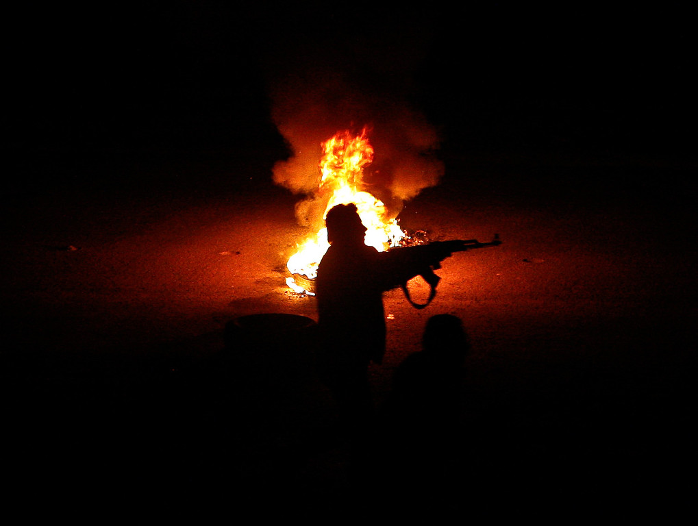 Description of . FILE - A Syrian rebel stands next to a flaming tire while firing at a Syrian army checkpoint in a suburb of Damascus, Syria, on Saturday, March 17, 2012. (AP Photo/File)