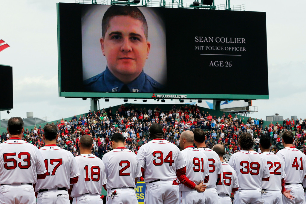 Description of . The Boston Red Sox line up during a tribute to victims of the Boston Marathon bombing and its aftermath, as an image of Massachusetts Institute of Technology Police Officer Sean Collier is displayed on the scoreboard, before a baseball game against the Kansas City Royals in Boston, Saturday, April 20, 2013. (AP Photo/Michael Dwyer)