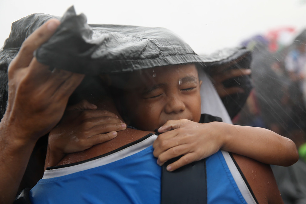 Description of . A child is seen trying to take shelter from the rain as they wait for a rescue flight in Tacloban Airport on November 14, 2013 in Leyte, Philippines. Typhoon Haiyan which ripped through Philippines over the weekend has been described as one of the most powerful typhoons ever to hit land, leaving thousands dead and hundreds of thousands homeless.   (Photo by Dan Kitwood/Getty Images)