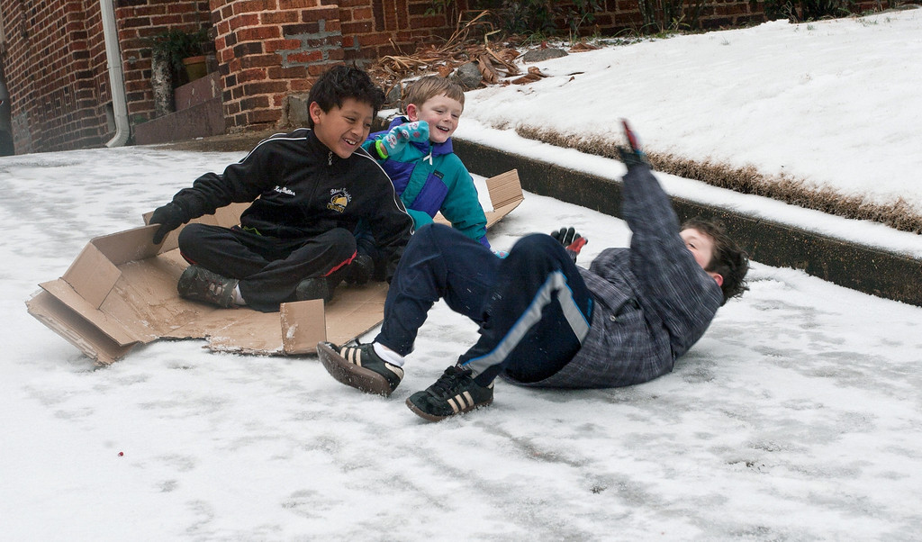 Description of . John Staton, right, tumbles off a makeshift cardboard sled as his friends laugh, on Feb 12, 2014, in Decatur, Ga. Icy road conditions caused some businesses and schools to shut down in the greater metro Atlanta region. (AP Photo/ Ron Harris)