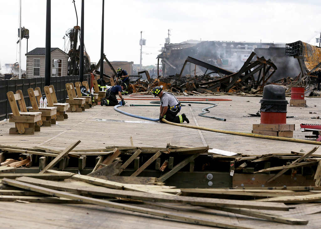 Description of . A firefighter unhooks two hoses at the place where emergency workers broke through the recently repaired boardwalk in efforts to stop a fire that broke out a day earlier at the Seaside Park boardwalk, Friday, Sept. 13, 2013, in Seaside Park, N.J. (AP Photo/Julio Cortez)