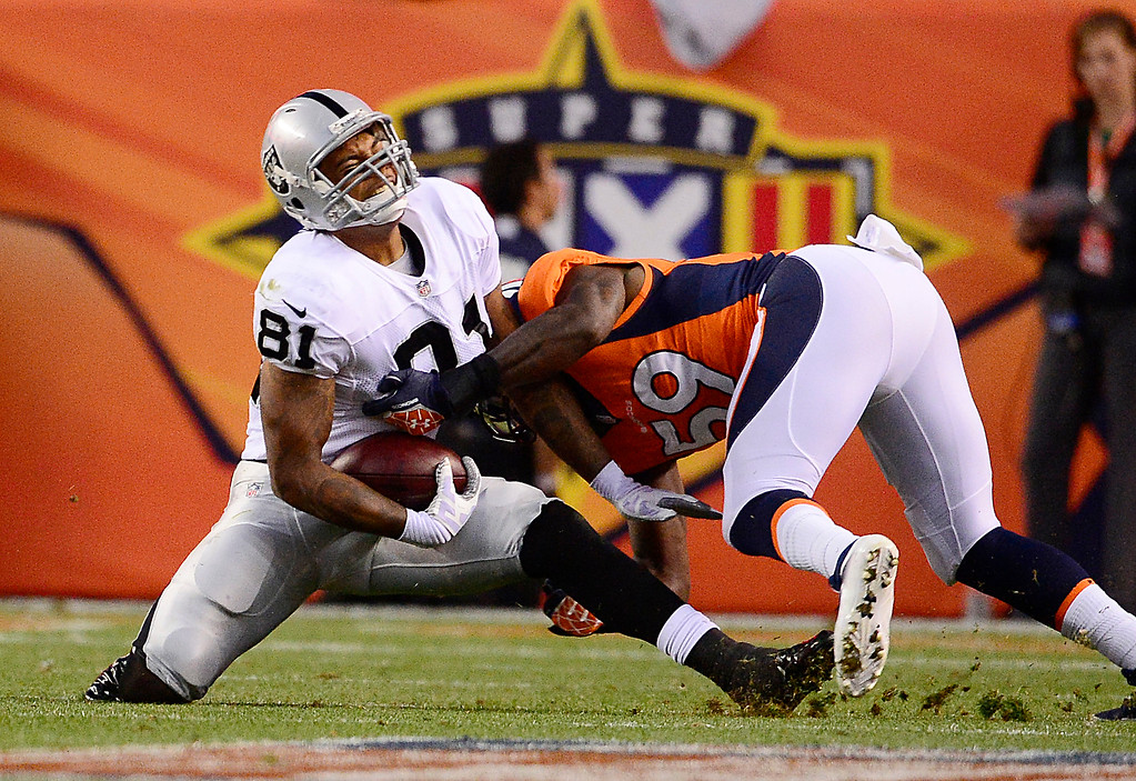 Description of . Denver Broncos linebacker Danny Trevathan (59) makes a tackle on Oakland Raiders tight end Mychal Rivera (81) in the first quarter. The Denver Broncos took on the Oakland Raiders at Sports Authority Field at Mile High in Denver on September 23, 2013. (Photo by AAron Ontiveroz/The Denver Post)